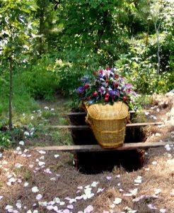 Wicker casket sitting above open grave